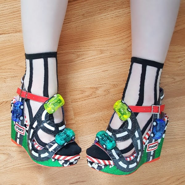wearing colourful wedge shoes with toy racing cars and road straps