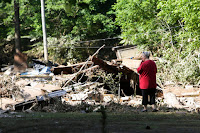 Emma Allen, 58, looks at the remnants of her damaged home after flooding in Falling Rock, West Virginia. (Credit: Marcus Constantino / Reuters) Click to Enlarge.