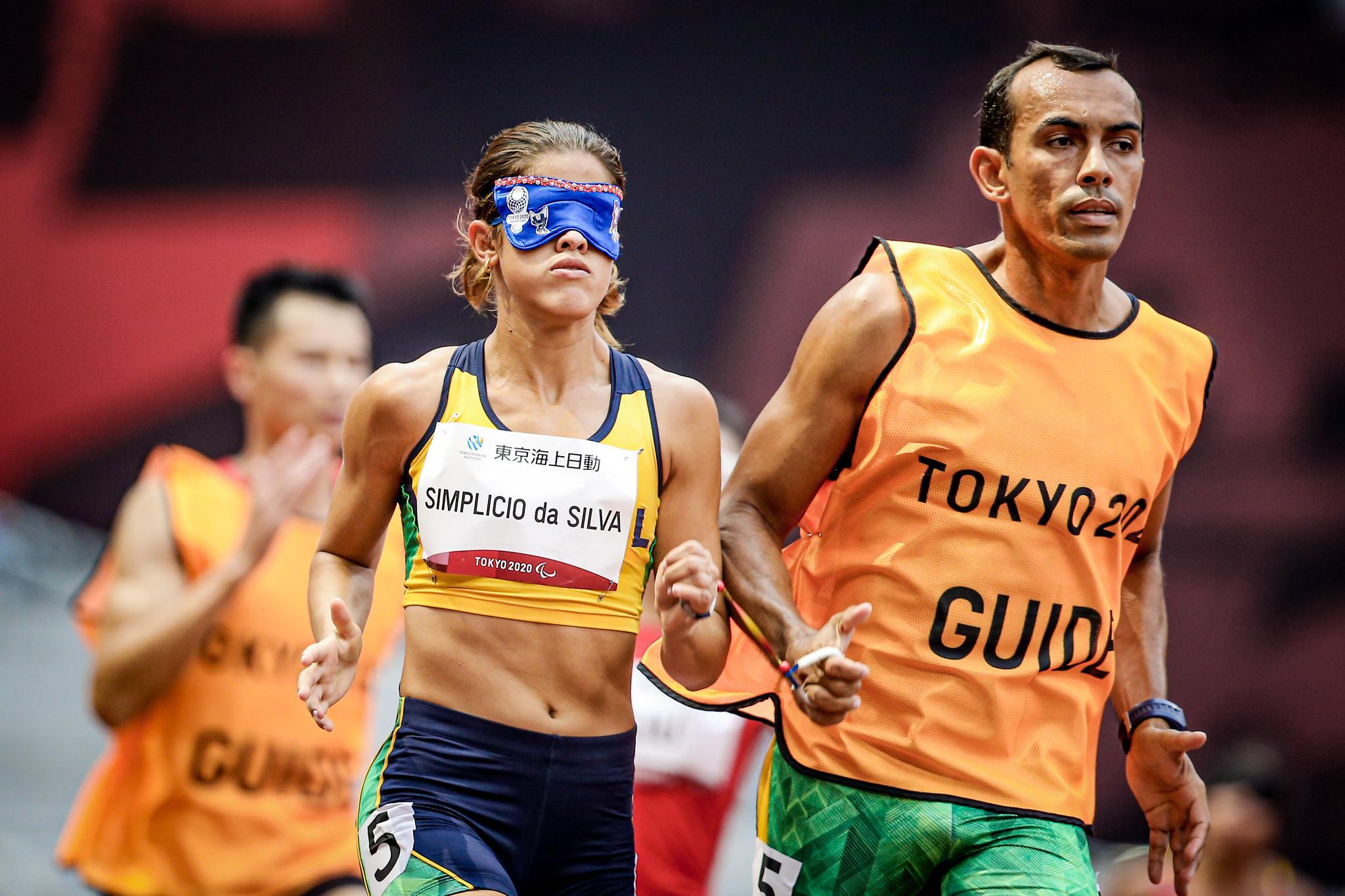 Thalita Simplicio e guia correm com uniforme da Tóquio 2020
