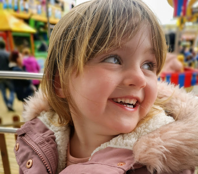Girl smiling and laughing whilst on a fairground ride at the British seaside town Skegness