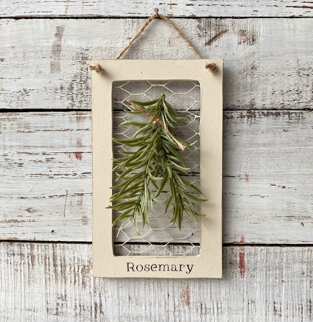 Photo of framed rosemary sprig on chicken wire