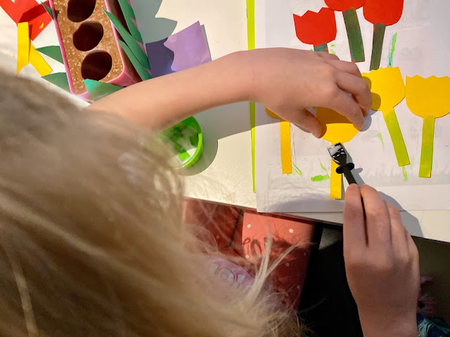 Close up of a girl putting glue on paper flowers