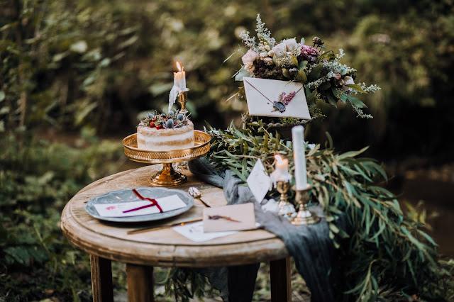 Ozdoby na weselny ślub: złote sztućce, szare talerze, papeteria od White Letters, złota patera, złote świeczniki, szary obrus i zielona girland z liści.
