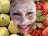 Tratamientos con frutas para el cuidado de la piel. Rostro de mujer con crema, rodeado por peras, uvas y naranjas