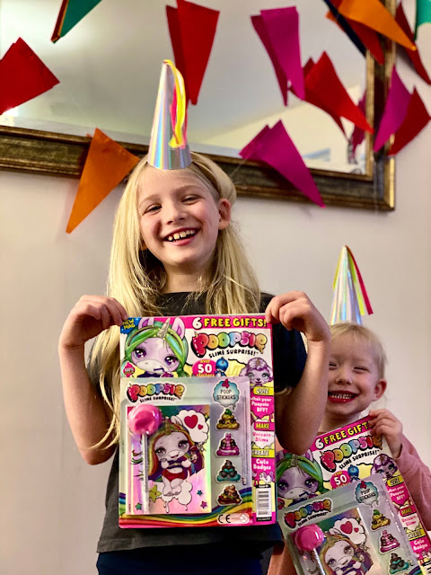 2 happy children in party hats in front of bunting holding Poopsie Slime Surprise Magazines issue 1