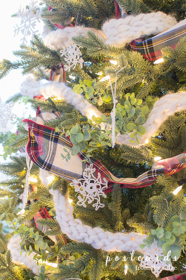 Chrismtas tree with plaid ribbon, crocheted snowflake ornaments, and baby eucalyptus sprays
