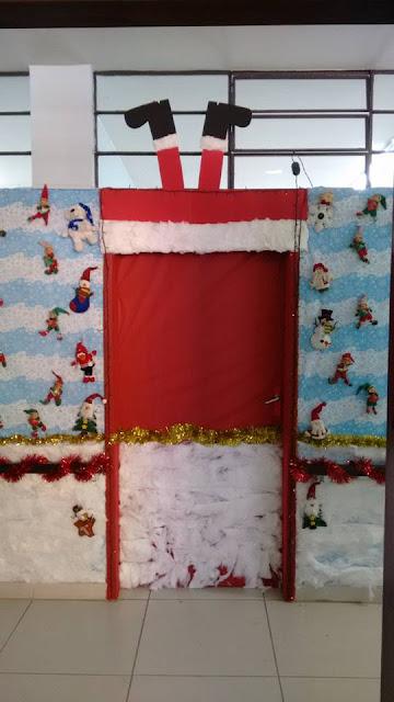 Decoração de porta natalina com Papai Noel descendo pela chaminé