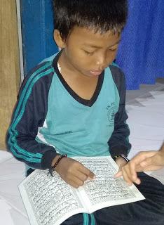 Yudistira, sedang belajar membaca Juz Amma didampingi oleh ibunya.