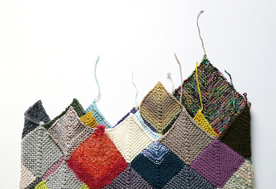 Colorful hand knit blanket made from worsted weight wool scraps in mitered square blocks with unwoven ends sticking up on a white background.