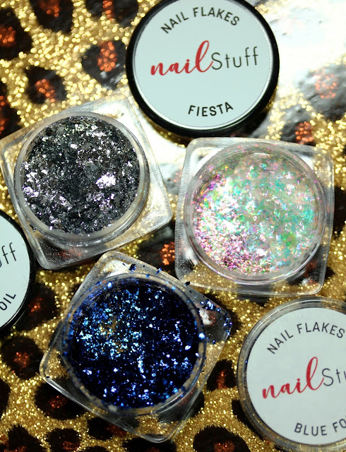 three small jars showing silver, blue and iridescent flakes for nail art