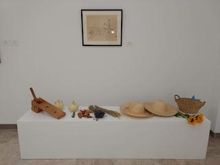 Cuadro del artista acompañado de botijos, sombreros de paja, machacador de aceitunas, y sustancias aromáticas naturales.