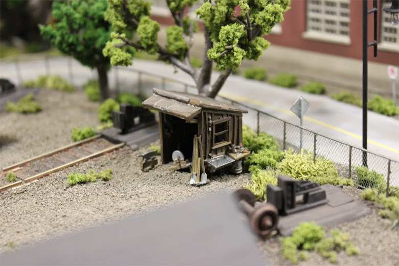 Woodland Scenics tool shed kit installed in a gravel rail yard scene