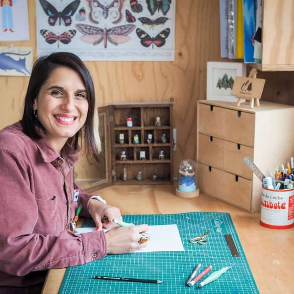 smiling woman working at desk in craft studio