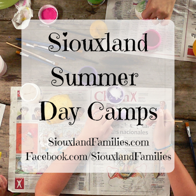 """in background, hands paint on a wooden table. a variety of craft supplies and newspaper are spread out on the table in front of them. in foreground """"Siouxland Summer Day Camps"""" and """"SiouxlandFamilies.com"""""""