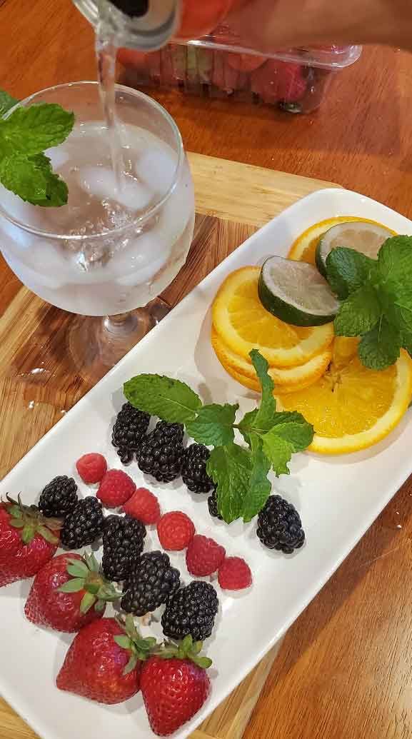 this is a plate of fresh berries with sparkling water in a wine glass and fresh mint
