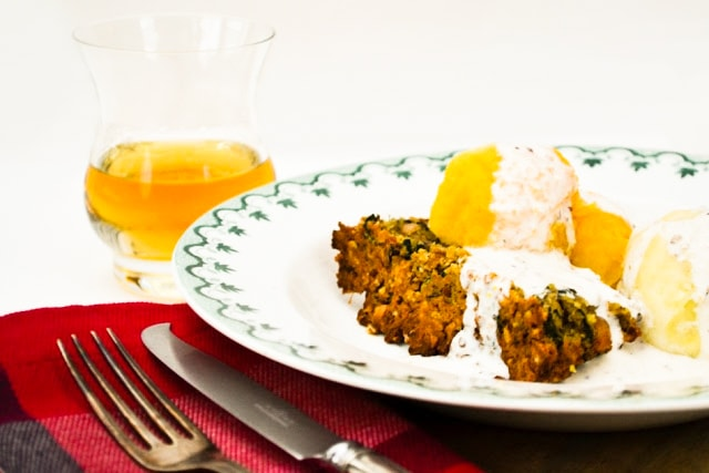 Vegan Haggis & Red Lentil Nut Loaf on a white plate with whisky cream sauce