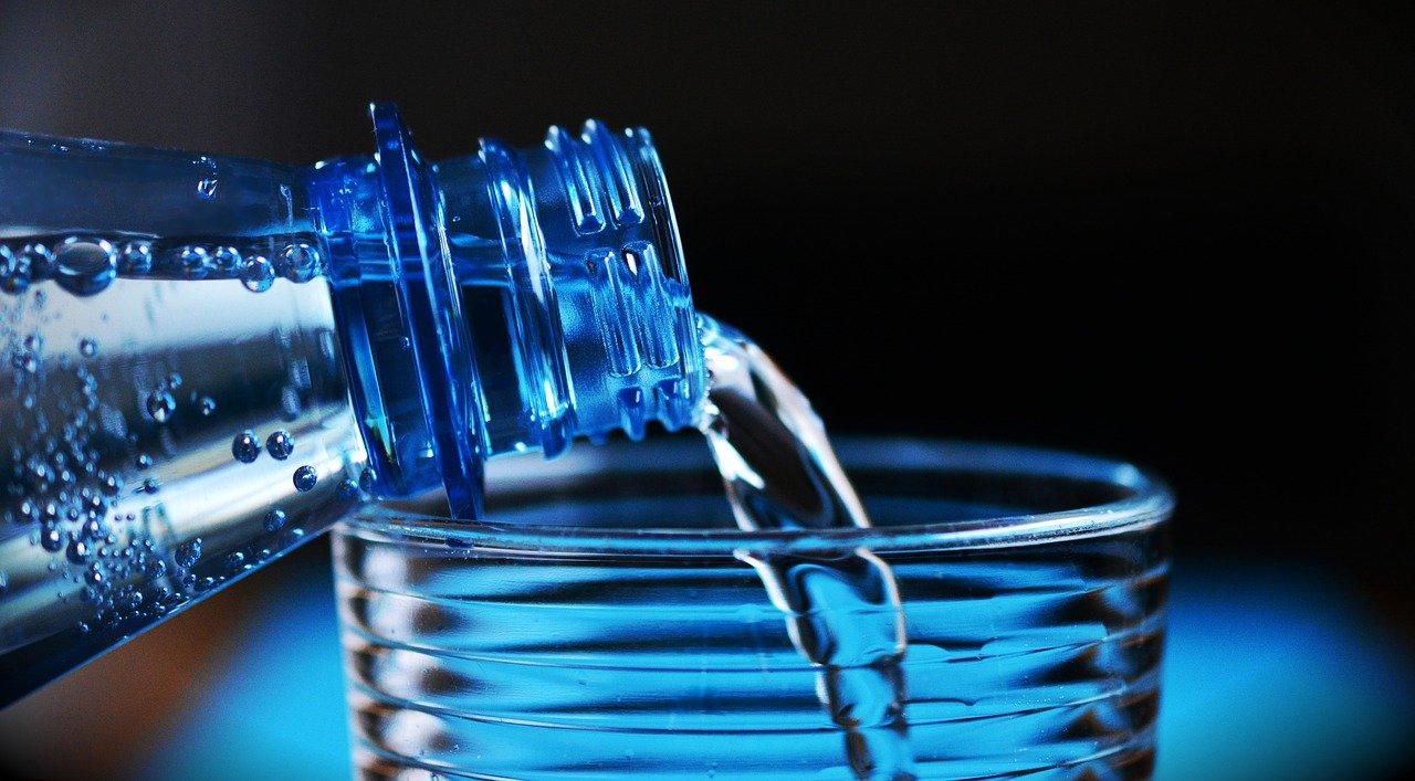 agua sendo despejada em copo de vidro