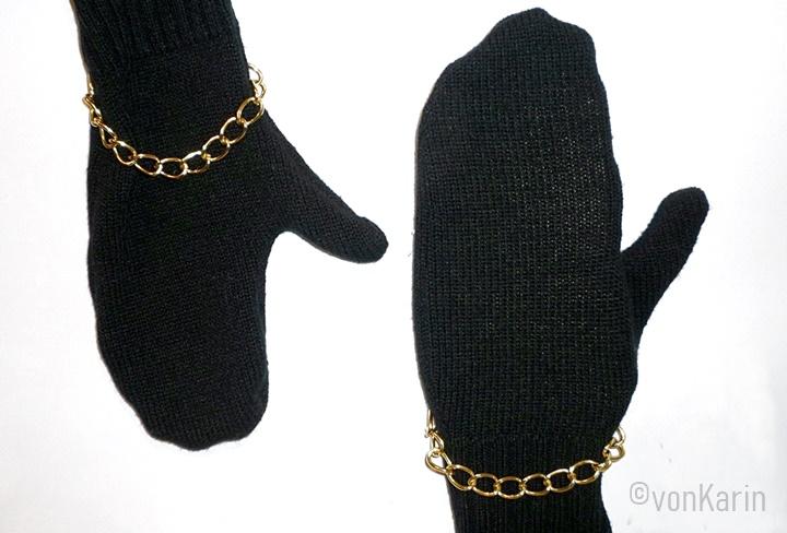 Zwei schwarze Strickhandschuhe mit goldener Kette