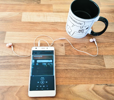 Phone playing music with Snoopy mug