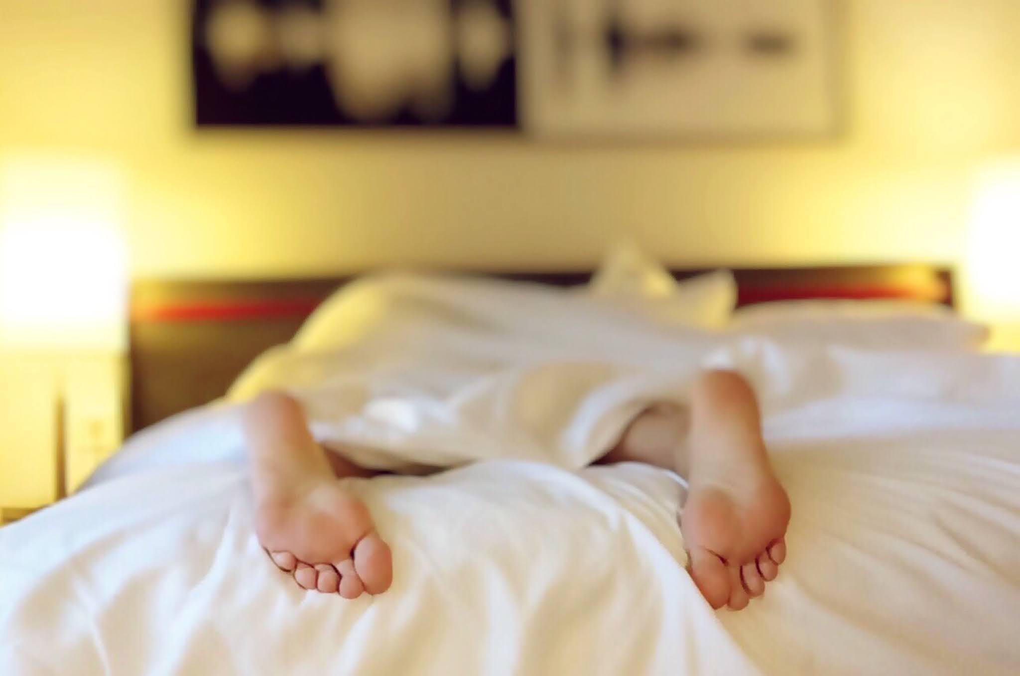 شخص يرقد على السرير يغطى بطانية بيضاء