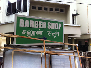 A multilingual sign in India. Barber shop (English) with the Indian English translation (saloon) in Tamil and Hindi.
