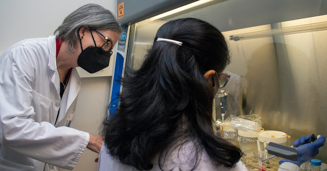 Dr. Kathleen Pratt assists someone with lab machinery