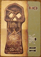 A card shown in the vertical orientation, with the long edge on the sides and the short edges on top and bottom. The left two thirds of the card has an aged parchment background, and there is a large image of the skull-shaped key from the Goonies film on it. Along the right side of the card, the background is a greyish green, and in the top of this section is a smaller version of the same image of the skull key, turned sideways. In the bottom of this section, also turned sideways, is a skull-and-crossed-swords pirate symbol next to the Roman Numeral Two.