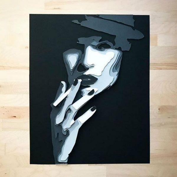 cut and layered paper portrait of woman's face with one hand holding cigarette, composed of black and gray tones