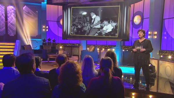 Photo from Swedish TV show showing the host, audience and my photo in the background