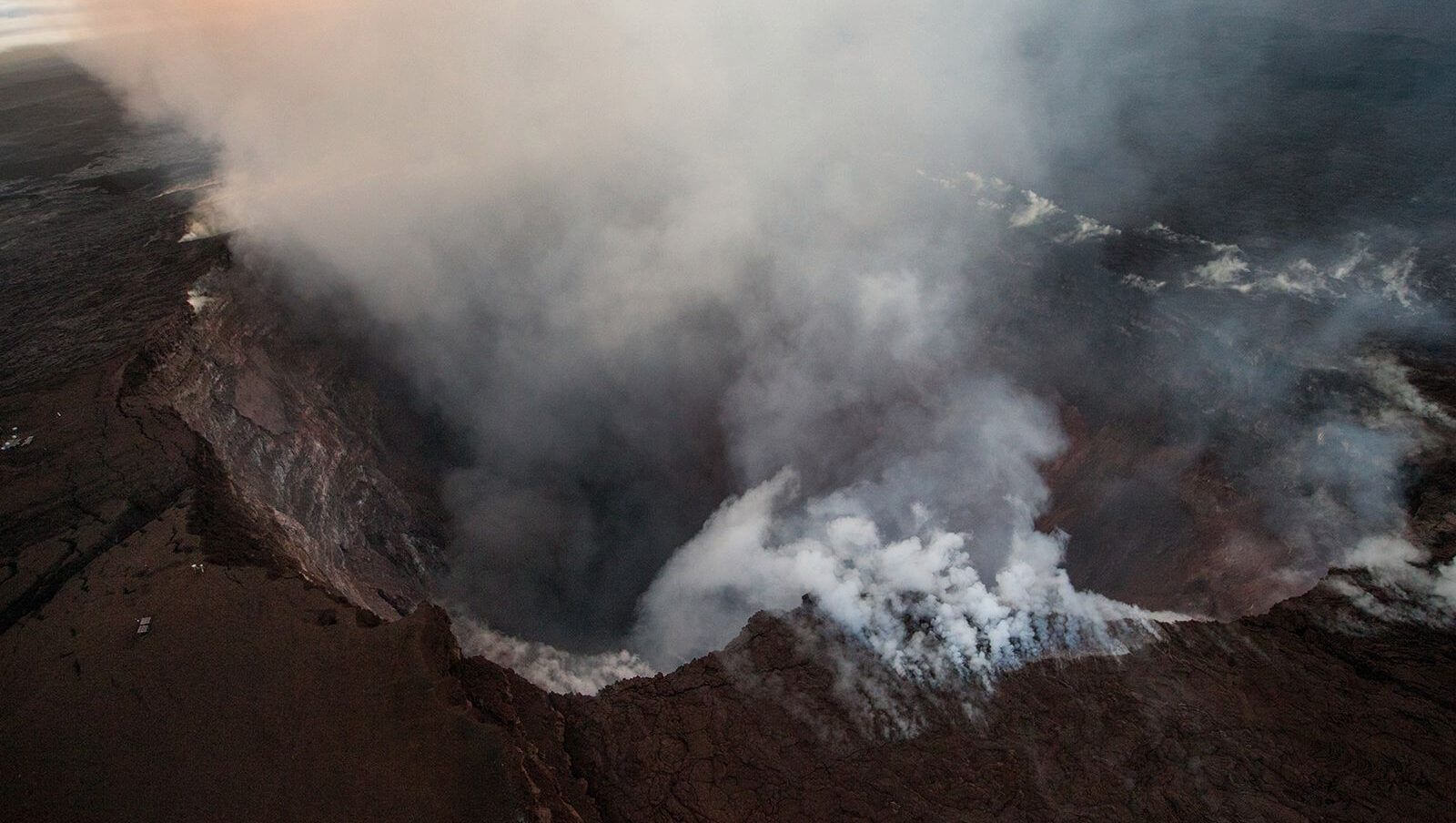 "Aerial shots over the Puʻu ʻŌʻō crater and other parts of Kilauea show smoke, steam, and ash emanating from the volcano, while other views have shown ""skylights"" or holes in the surface that reveal lava flowing Dramatic Photos of Hawaii's Volcano below."