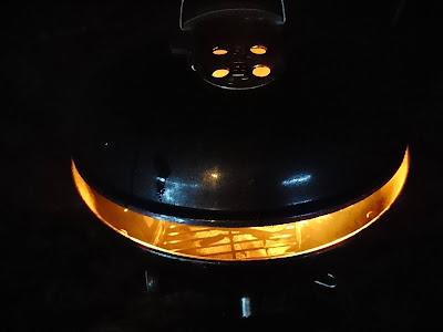 Grill im Dunkel, Deckel zum Teil geöffnet, oranges Licht des Feuers leuchtet durch die Schlitze.