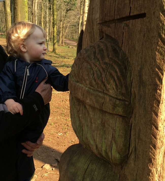 toddler touching the wooden sculpture