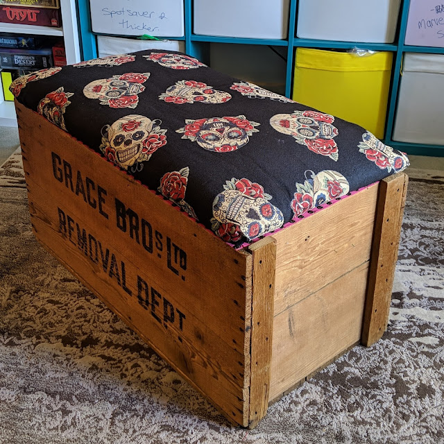 """Photo of wooden crate with lid closed placed at an angle to show the side, with fabric covering the lid. The fabric is of skulls and flowers. The front of the crate says """"Grade Bros Ltd Removal Dept""""."""