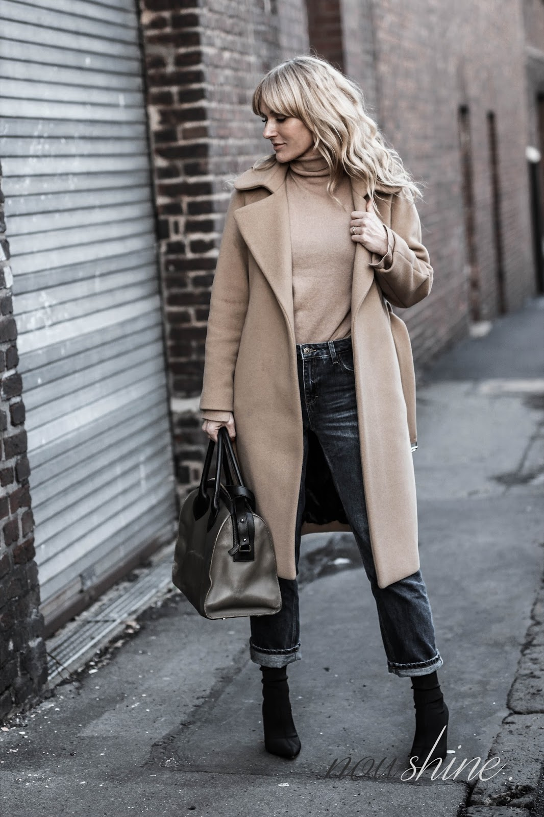 Nowshine trägt einen Mantel und Rolli in Camel, dazu Jeans und Sockboots/ Ü40 Fashion Blog
