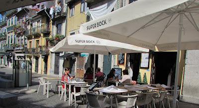 Pessoas sentadas numa explanada próximo de algumas casas do Porto
