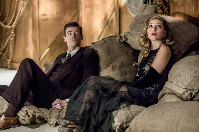 A screencap of Barry Allen and Kara Danvers sitting on a pile of flour sacks in a warehouse. They both wear 1920s clothing: Barry, a dark three-piece suit, and Kara, a black full length evening gown with a glittery bodice and elbow-length gloves.