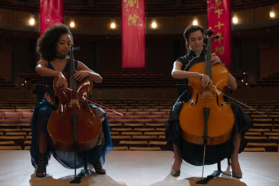 Movie still for the movie The Perfection where Logan Browning and Allison Williams play a cello duet in a concert hall