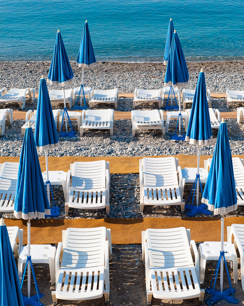 a photo of lounge chairs on a beach in nice france by daniel south