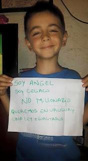 """Niño con el cartel escrito a mano que dice: """"Soy Ángel. Soy celíaco, no millonario. Queremos en Uruguay una ley igualitaria""""."""