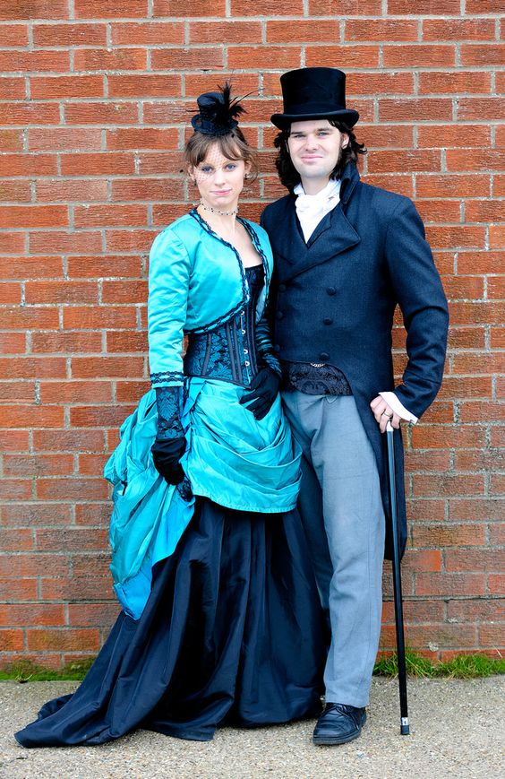 Couple wearing matching steampunk costumes in turqoise and navy blue. steampunk fashion for men and women