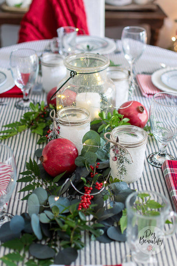 Christmas centerpiece with greenery, candles and pomegranates