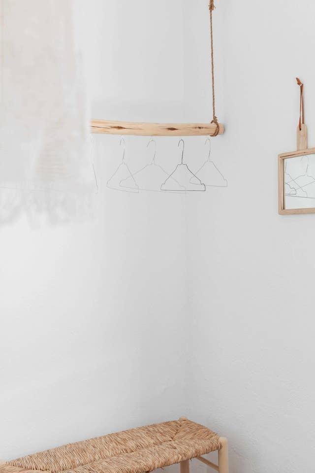 Interior blanco con madera natural, mimbre y un perchero hecho de una rama