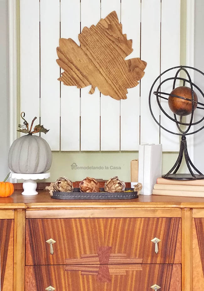 wooden antique buffet with armillary sphere, wooden leaf wall art, gray pumpkin on stand and artichokes in tray