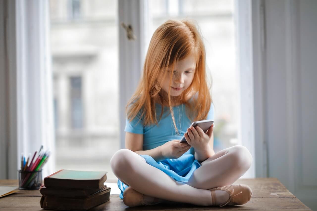 niña utilizando teléfono celular