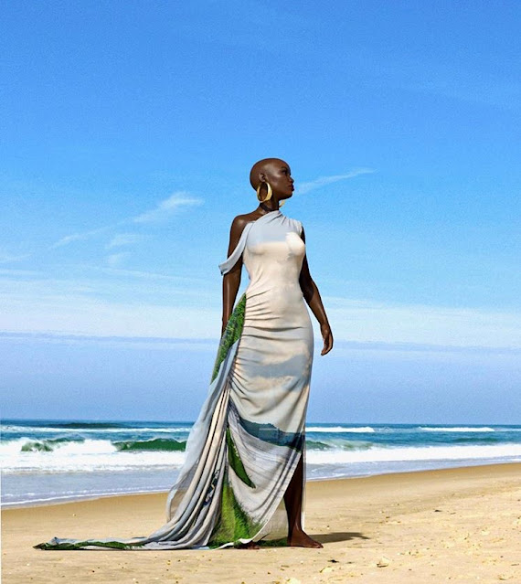 A mannequin standing on a beach wearing a dress with a white, blue and green pattern.