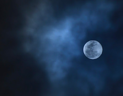 An image of a full moon, slightly covered by clouds