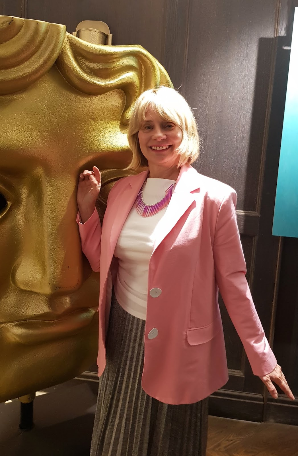 Wearing pink and silver Is This Mutton blogger Gail Hanlon poses with the BAFTA statue