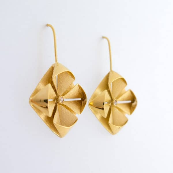 golden folded metal earrings with tiny crystal in center of each