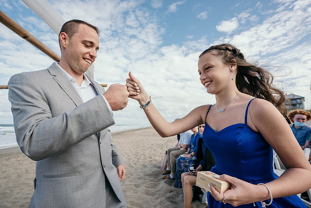 Groom fist bumping Bridesmaid at Ceremony