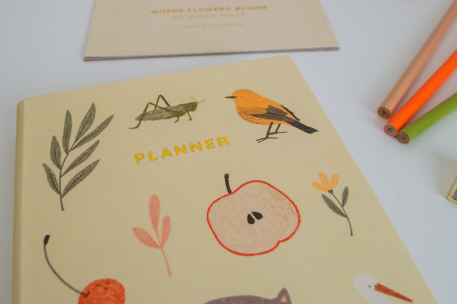 Close up of the cover of a planner with animals and plants on the front